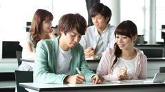 Young university students chatting and studying together in a classroom - stock footage