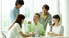 Smiling university students chatting together Stock Footage