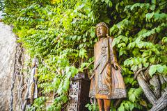 figures and wood carvings surrounded by ivy and vegetation - stock photo