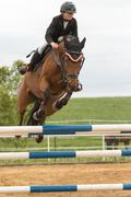 Closeup view of horsewoman jumping. Vertically. - stock photo