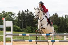 Horsewoman in red jacket is jumping on a white horse - stock photo