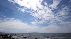Sea lapping rocky coast, spectacular sky sun, sunburst, timelapse - stock footage