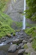 Columbia River Gorge waterfall and greens. - stock photo