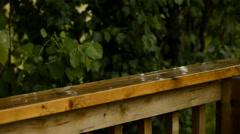 Rain falling on deck railing Stock Footage