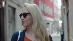 Tourist blonde looking around, with sunglassess on, in slow motion Stock Footage