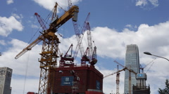 Cranes work at a construction site on a sunny day in Beijing's central business - stock footage