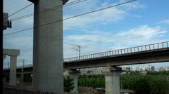 A CRH (China Railway High-speed) train runs past overhead railway Stock Footage