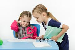 Girl teacher checks written by a disciple - stock photo