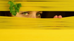 Green eyed mysterious woman looking through pasta roller blind, close up Stock Footage