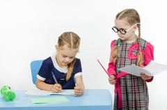 Privlezhnaya pupil under the supervision of a strict teacher Stock Photos
