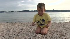 Boy playing with pebbles on the beach - stock footage