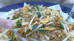 Close up of woman's hand eating   Pad Thai stir-fried rice noodles Stock Footage