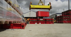 Industrial crane loading and unloading cargo containers at a busy port. Stock Footage