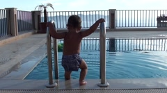 Toddler in cloth diaper plays near swimming pool Stock Footage