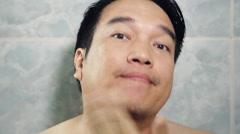Happy Asian man shaving beard high definition video Stock Footage