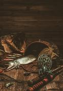 Fishing tools and fresh pike on a wooden table - stock photo
