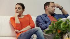 Offended couple sitting on sofa at home HD Stock Footage