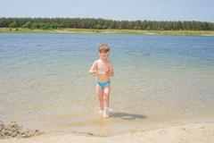 The boy in water on a lake beach. - stock photo