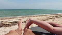 The legs of two people are sunbathe on the beach by the sea - stock footage