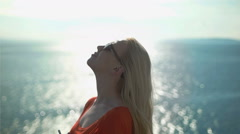 Blonde girl twisting next to the seaside and enjoying - stock footage