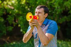 The man in the street holding a plastic speaker shouts on a blue Stock Photos