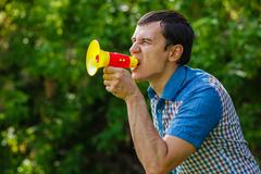 The man in the street holding a plastic speaker shouts on green - stock photo