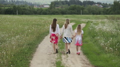 Mother and daughters walking holding their hands Stock Footage