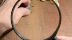 Viewing of old coins through magnifying glass Stock Footage