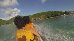 Riding on a water banana and flipping over at the end Stock Footage