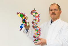 Biology teacher showing DNA model - stock photo