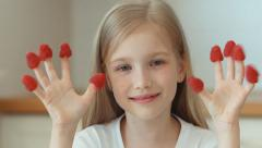 Closeup portrait girl indulges with raspberries and laughing at the camera Stock Footage