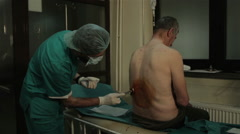Anesthesiologist preparing patient for anesthesia, lubricates iodine on the back Stock Footage