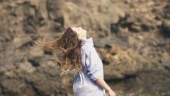 Sexy woman in mens shirt throwing her hair on rocks by sea HD Stock Footage
