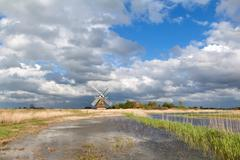 Charming windmill bu river and cblue sky with clouds Stock Photos