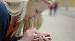 Blonde girl waring stripes typing on the phone Stock Footage
