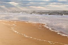 sunbeams over North sea beach - stock photo