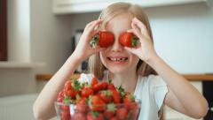 Closeup portrait of a girl with strawberry eyes. Child smiling at the camera Stock Footage
