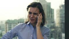 Sad, troubled woman talking on cellphone on terrace, super slow motion HD Stock Footage