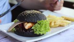 Big black burger with fries on a plate close up Stock Footage