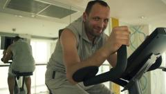 Happy smiling man riding stationary bike HD Stock Footage