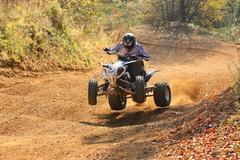 ATV rider goes up the hill Stock Photos