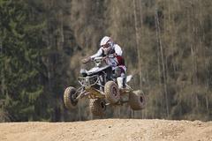 Rider jumps on quad motorbike - stock photo