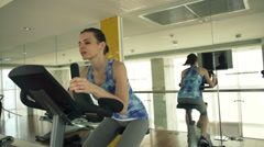 Tired woman riding stationary bike in gym HD - stock footage