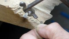 Goldsmith is cutting a silver piece to make a pendant cross - stock footage
