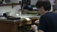 Goldsmith preparing the polishing tool to work on a gold ring - stock footage