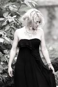 beautiful and delicate blonde woman in black long dress - stock photo