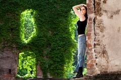 Brunette wearing torn jeans and black t-shirt, with daring attitude. - stock photo