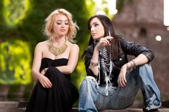 Two attractive gorgeous women with contrasting dressing styles - stock photo