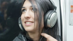 Young woman listening music on the metro train: underground, subway Stock Footage