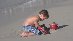 Young boy playing with toys on beach, Cape Town,South Africa Stock Footage